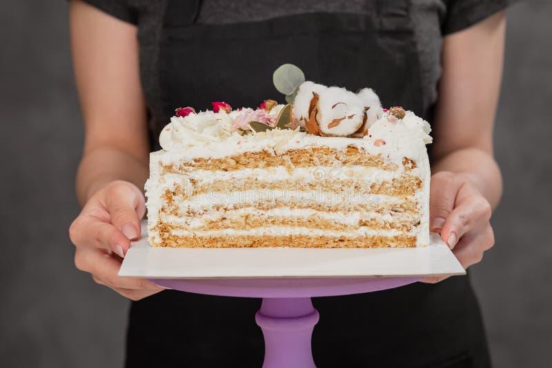 Halva en kaka Närbild av en klippt kaka med synlig lager och fyllning onditer rymmer kakan i hans händer arkivbilder
