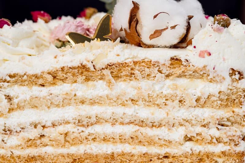 Halva en kaka Närbild av en klippt kaka med synlig lager och fyllning onditer rymmer kakan i hans händer royaltyfri bild