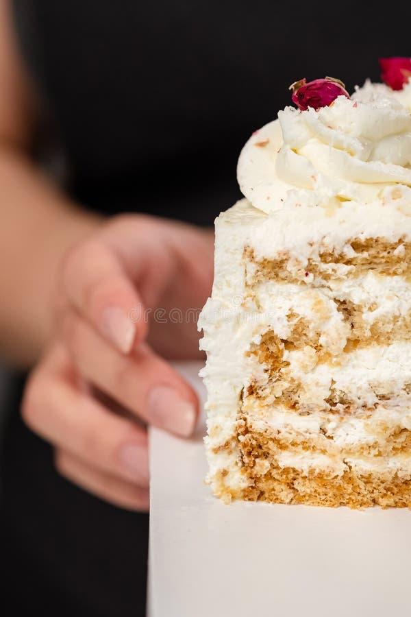 Halva en kaka Närbild av en klippt kaka med synlig lager och fyllning onditer rymmer kakan i hans händer arkivfoton