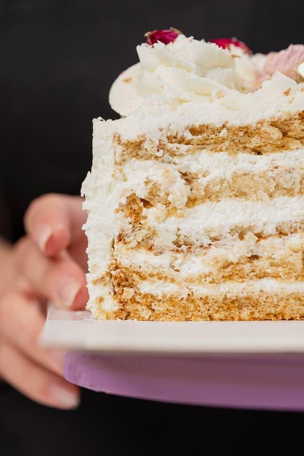 Halva en kaka Närbild av en klippt kaka med synlig lager och fyllning onditer rymmer kakan i hans händer royaltyfria foton