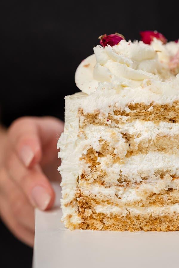 Halva en kaka Närbild av en klippt kaka med synlig lager och fyllning onditer rymmer kakan i hans händer fotografering för bildbyråer