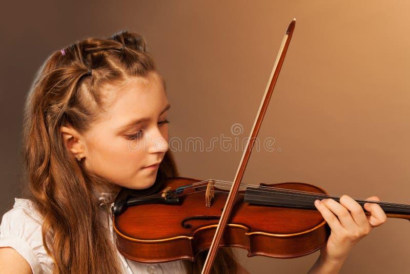 Halva-framsida sikt av den härliga flickan som spelar fiolen arkivfoton