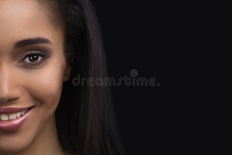 Halva-framsida stående av den härliga le känsliga afro amerikanska kvinnan på mörk bakgrund royaltyfri fotografi
