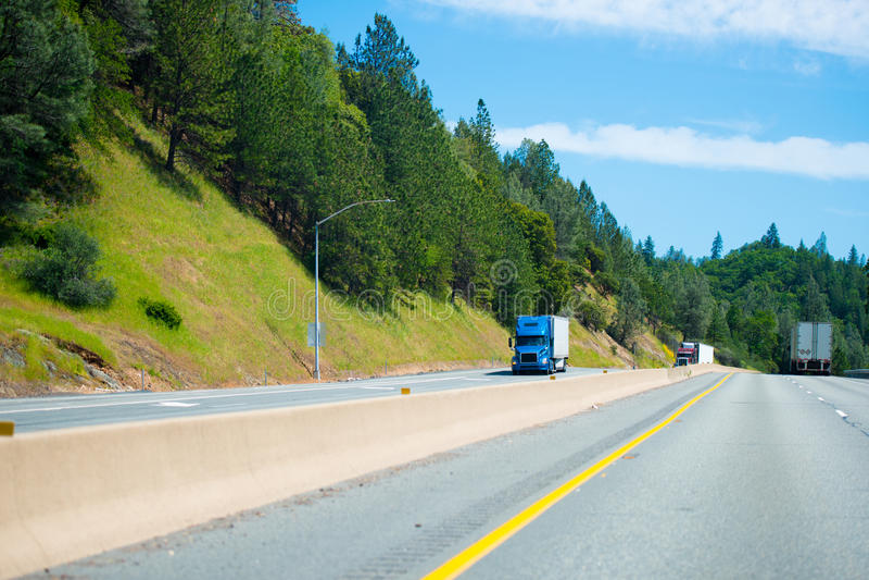 Halva lastbilar med halva släp flyttar sig uppåt- och neråt skiljelinjen arkivbild