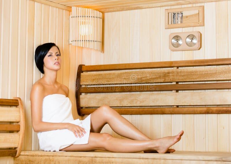 Halva-naken kvinna som kopplar av i bastu arkivfoton