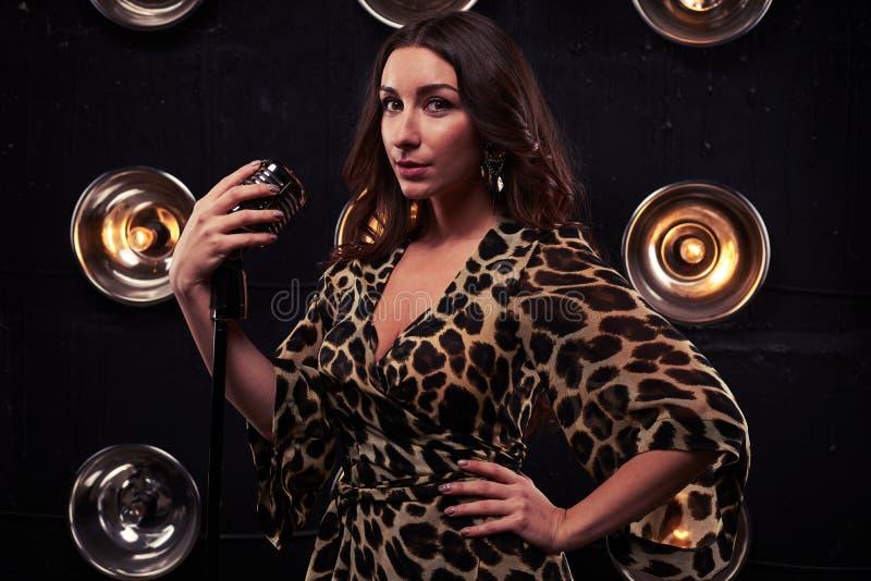 Halva-vänd modell i en chiffongleopardklänning som rymmer en silverst royaltyfri fotografi