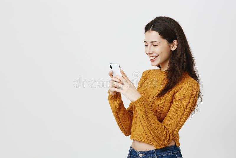 Halva-vänd stående av det trendiga gulliga kvinnliga messaging- eller tafotoet på smartphonen, medan le i huvudsak och arkivbilder