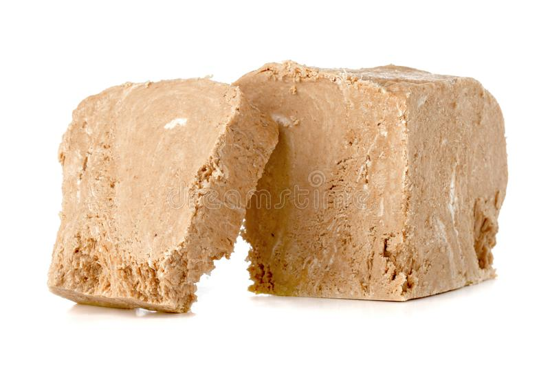Halva on a white background. Arabian sweetness of caramel mass and ground roasted kernels of nuts, peanuts, close-up stock image