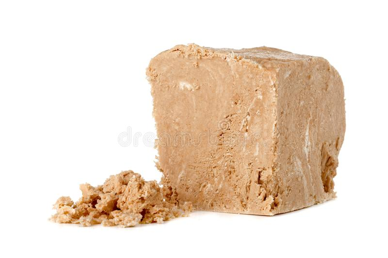 Halva on a white background. Arabian sweetness of caramel mass and ground roasted kernels of nuts, peanuts, close-up royalty free stock image