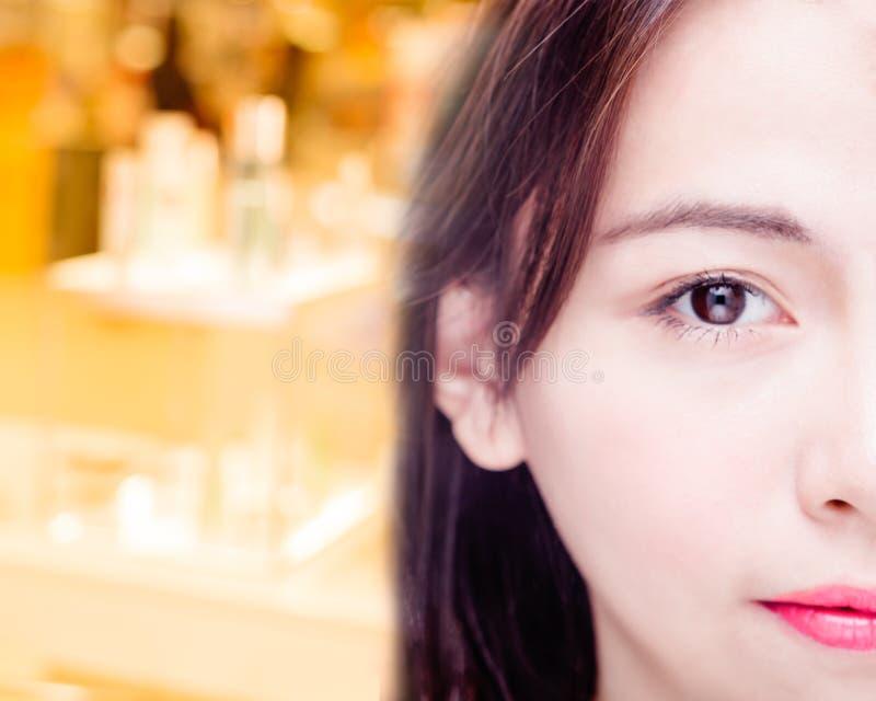 Halvan av den asiatiska framsidan för kvinna` s med skönhetsmedel kontrar defocused i b arkivbilder