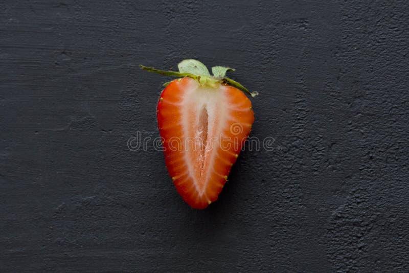 Halvan av jordgubben, röd härlig jordgubbenärbild för snitt, på en svart mörk konkret bakgrund Bl?sa utskjutande Meloe Frukteroti royaltyfri bild