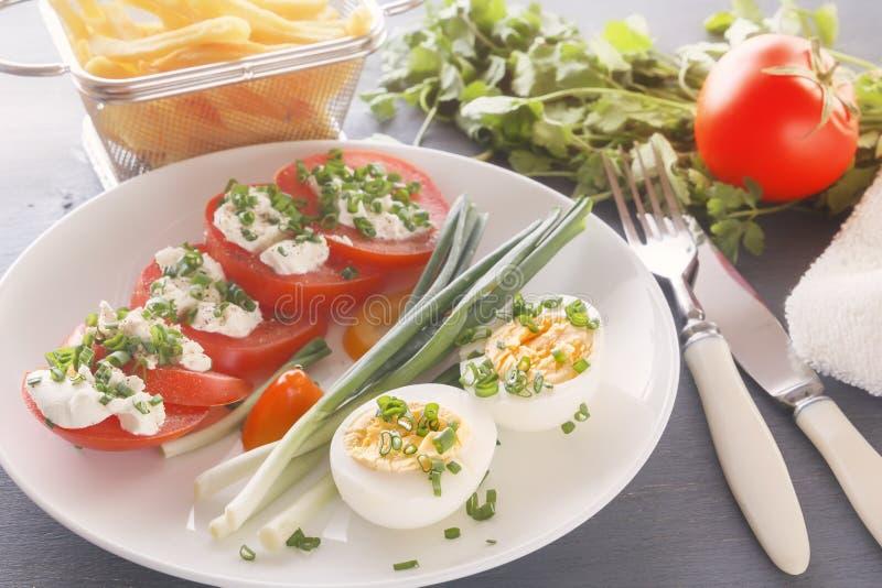 Halvan kokade ägg med tomater, salladslökar som strilades med gräsplaner i en vit platta på en grå trätabell royaltyfria foton