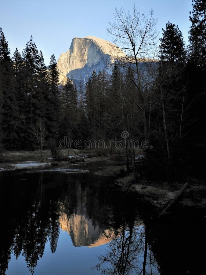 Halve die Koepel Merced-Rivier in de Winter bij het Nationale Park van Yosemite wordt overdacht stock afbeelding