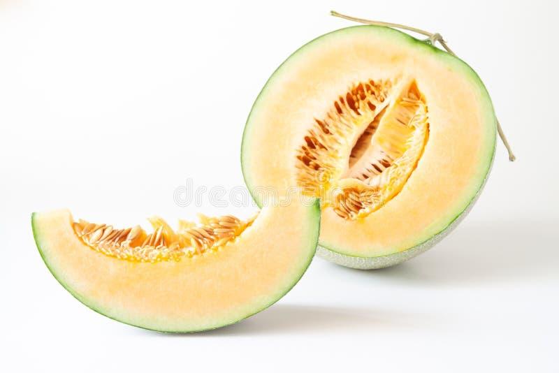 Halve en gesneden Japanse die meloenen op witte achtergrond worden geïsoleerd stock afbeeldingen