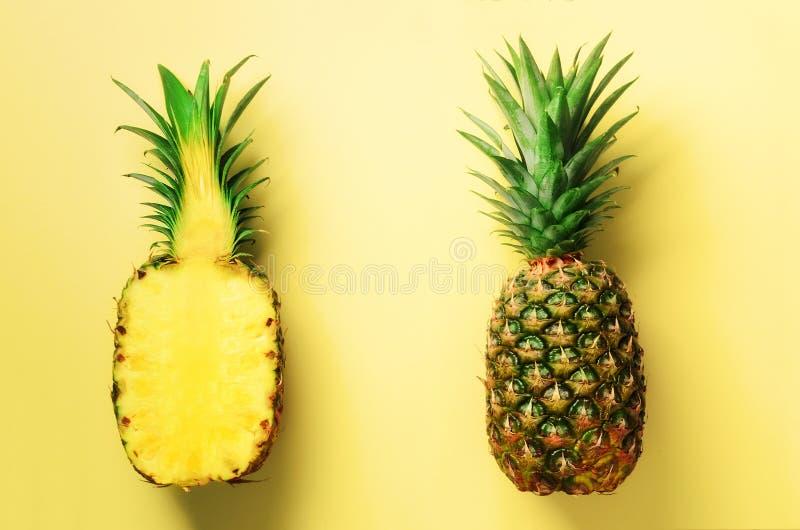 Halve plak van verse ananas en geheel fruit op gele achtergrond Hoogste mening De ruimte van het exemplaar Helder ananassenpatroo royalty-vrije stock afbeeldingen