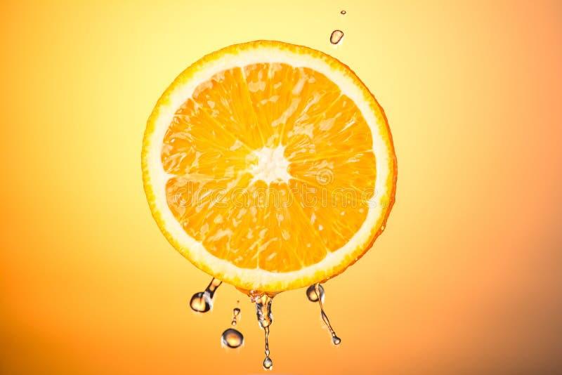 Halve sinaasappel met plonsen van water op een gekleurde achtergrond, concept het gezonde eten royalty-vrije stock foto's