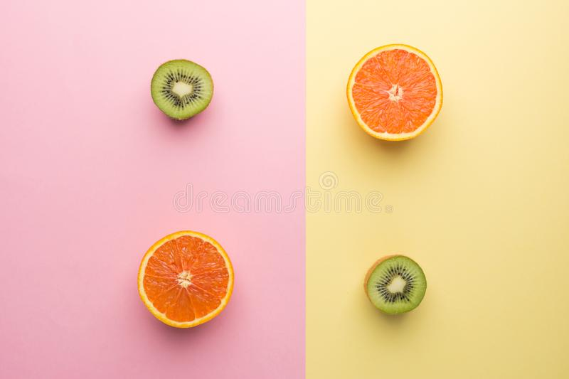 Halve Sinaasappel twee en Halve Kiwi Twee op Achtergrond van de Meetkunde de Gele Roze Pastelkleur, Hoogste Mening royalty-vrije stock foto's
