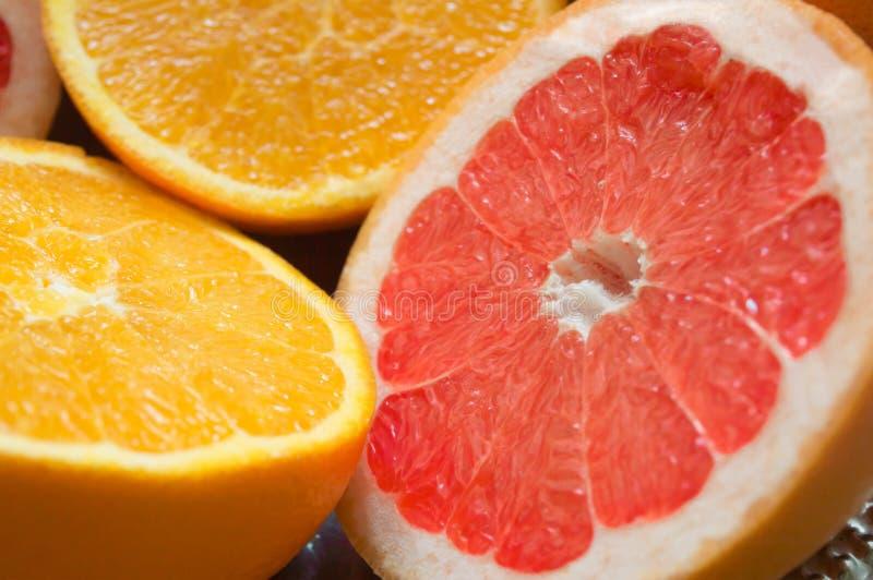 Halve stukken kleurrijke grapefruits en sinaasappelen royalty-vrije stock afbeeldingen