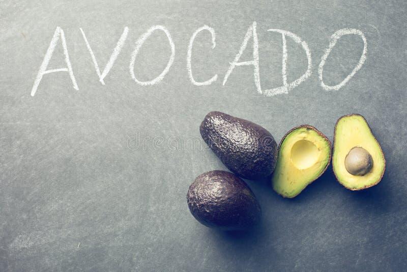 Halved avocado on blackboard. The halved avocado on blackboard royalty free stock photos
