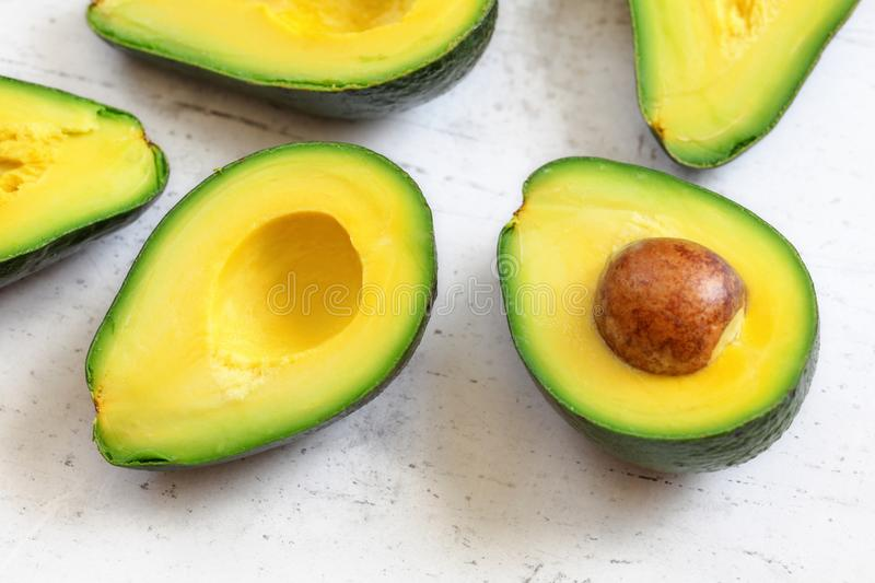 Halved avocado fruits closeup with green yellow pulp, brown seeds visible on white working board.  royalty free stock photography