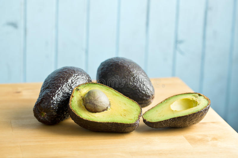Halved avocado on kitchen table. The halved avocado on kitchen table stock photography