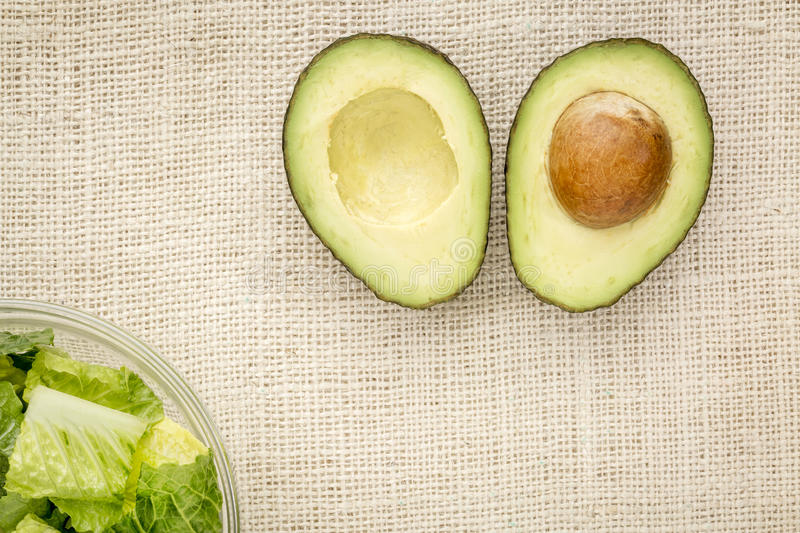 Halved avocado and lettuce. Halved avocado and a bowl of romaine lettuce against burlap canvas stock photography