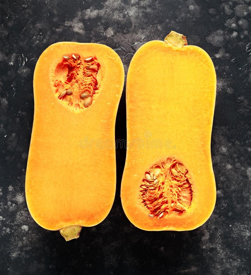 Halved butternut squash in a black background, vintage royalty free stock photo