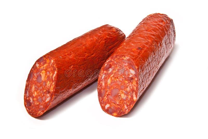 Halved Chorizo sausage. Closeup of halved chorizo sausage isolated on white background royalty free stock images