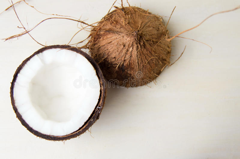 Halved coconut on a wooden table. Halved coconut fruit on a wooden table stock images