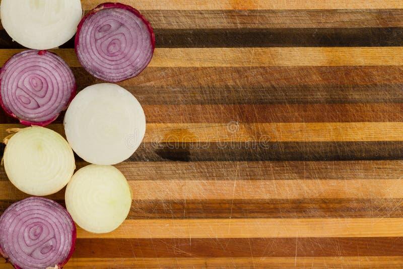 Halved cortou a beira fresca da cebola em madeira listrada fotografia de stock royalty free