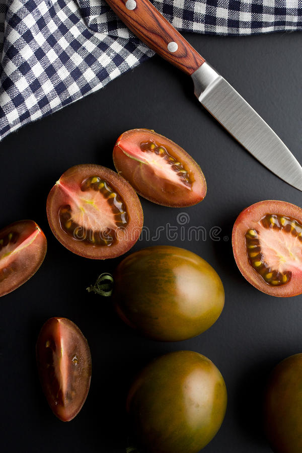 Halved dark tomatoes. On black background royalty free stock images