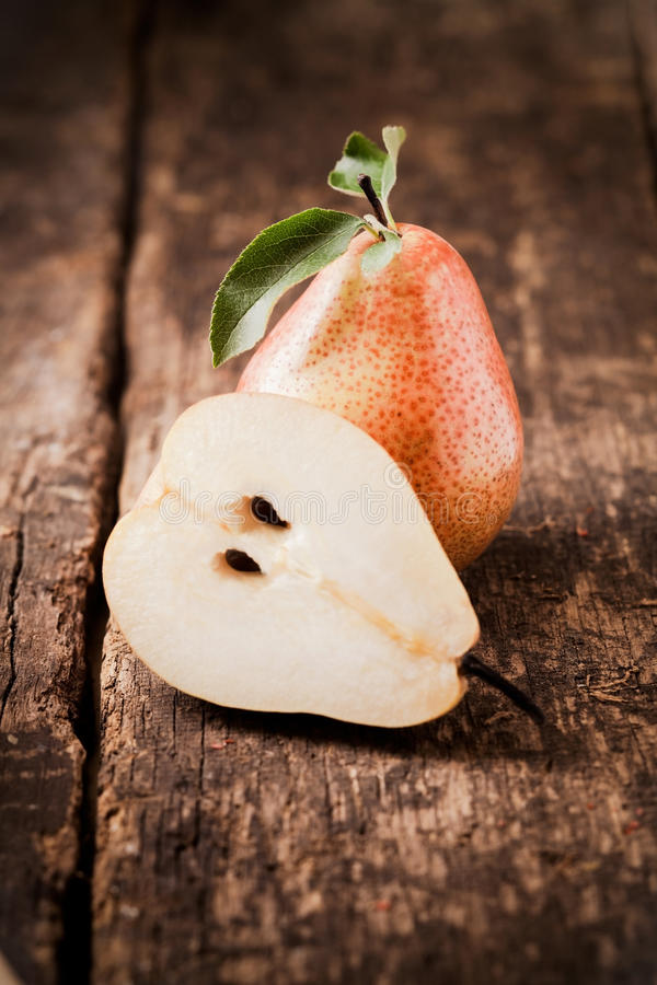 Halved fresh juicy pear. Balanced against a whole fruit on a rough wooden table top royalty free stock photo