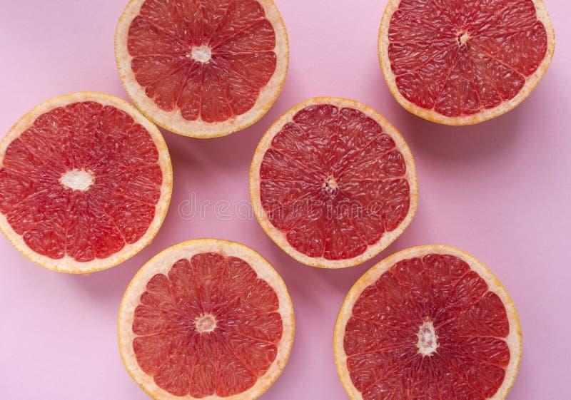 Halved grapefruit on pastel blue background stock images