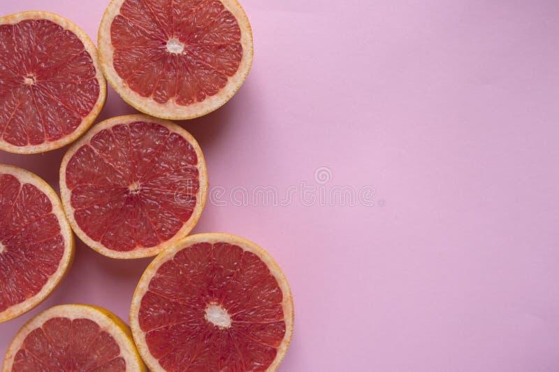 Halved grapefruit on pastel blue background stock photography