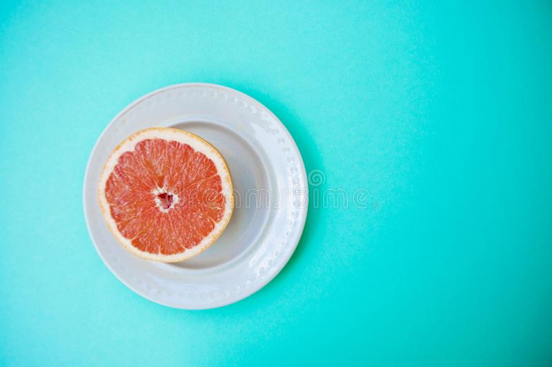 Halved grapefruit on pastel blue background. stock photo