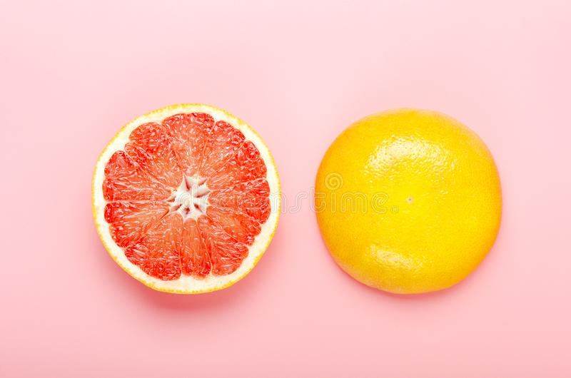Halved grapefruit on a pink background. Refreshing summer tropical fruit. Minimal composition. Top view, flat lay. stock image