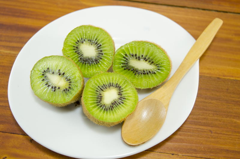 Halved kiwis on a white plate stock photography
