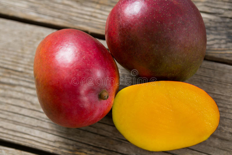Halved mangoes on wooden table. Close-up of halved mangoes on wooden table royalty free stock image