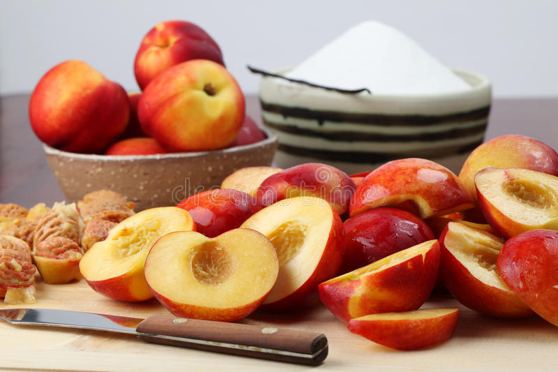 Halved nectarines. On a cutting board for jam making royalty free stock photo