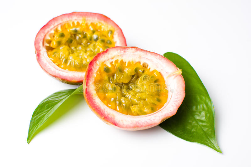 Halved passion fruit with leaves on white. Halved passion fruit with leaves isolated on white royalty free stock photos