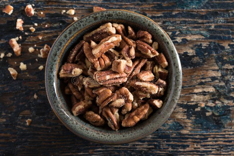 Halved Pecans in a Bowl. Top view of raw halved pecans in a small bowl royalty free stock photo
