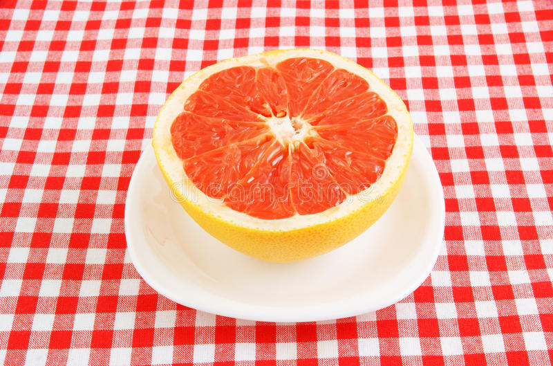 Halved Red Grapefruit On Tablecloth Royalty Free Stock Photography