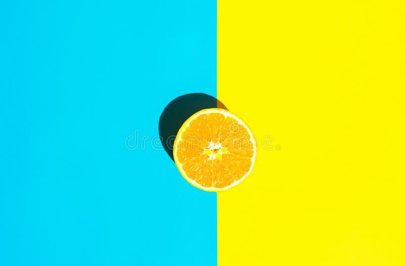 Halved Ripe Juicy Orange on Vivid Duotone Blue Yellow Background. Bright Harsh Sunlight Deep Shadow. Vibrant Neon Colors. Summer Tropical Vacation Travel royalty free stock photography