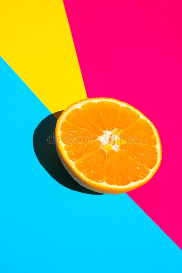 Halved Ripe Juicy Orange on Vivid Fuchsia Blue Yellow Background. Bright Harsh Sunlight Deep Shadow. Vibrant Neon Colors. Summer Tropical Vacation Travel stock images