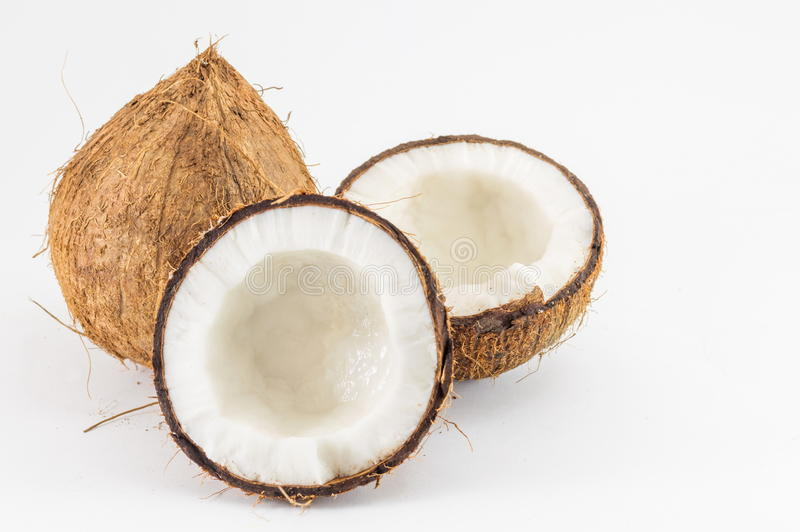 Halved and whole fresh coconuts with leaves. Halved and whole fresh coconuts with coconut leaves on white royalty free stock image