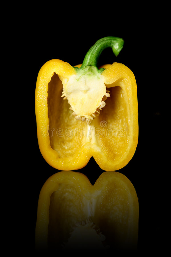 Halved yellow bell pepper. Reflecting on black background royalty free stock photos