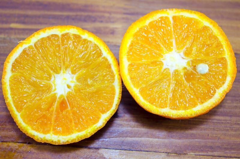 Halverad apelsin på ett trätabellslut upp royaltyfria bilder