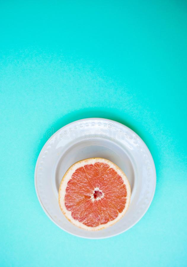 Halverad grapefrukt på pastellblåttbakgrund arkivbilder