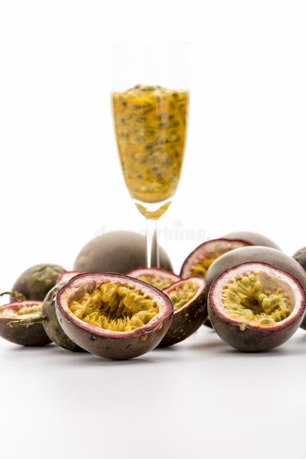 Halverad Passionfruits och fruktträmassa i ett exponeringsglas arkivfoto