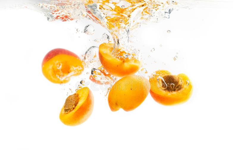 Halves of apricots dropped into water an sinking. Bunch apricots halves dropped into water with splash and air bubbles on white background royalty free stock photo